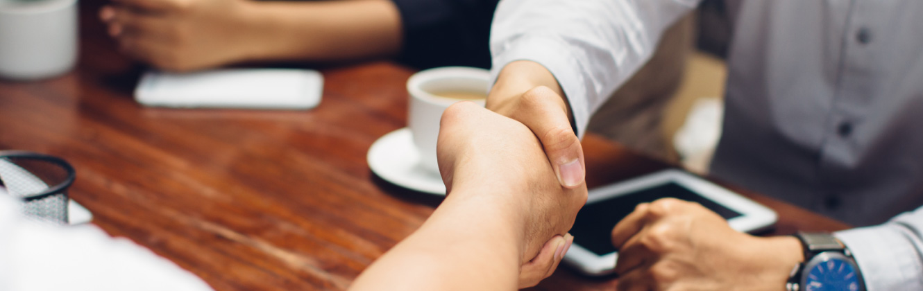 Two people shaking hands over coffee