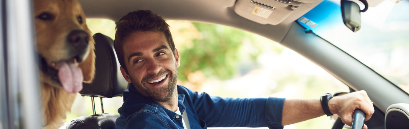 a man smiling at dog in car